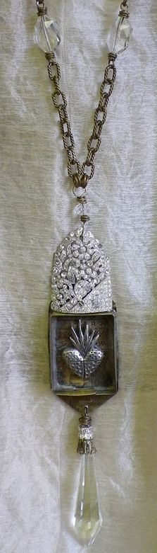 necklace featuring a sacred heart milagro inside a small box. Old rhinestone piece on top and a dangling chandelier crystal below. No idea whose work this is, the link is broken, but I love this.