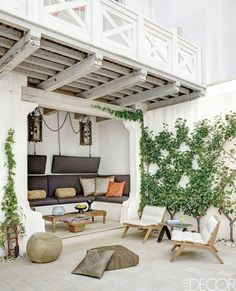 In this Mississippi family's Florida Gulf Coast home, architect Michael Imber and designer Lynn Myers conjure a whitewashed Moroccan fantasy, which includes a courtyard holding teak lounge chairs by Henry Hall Designs, a custom-made banquette with cushions in a Perennials fabric, and antique Spanish lanterns found in Belgium.
