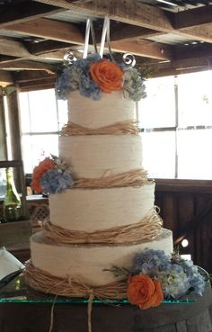 A beautiful rustic wedding cake for my friend.  Buttercream icing, funfetti cake (groom's favorite). Finished with raffia ribbon, blue hydrangea and coral roses.