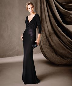 COIMBRA. Elegant long mermaid dress with 3/4 sleeves and a v-neckline. An understated dress full of unique details, such as an exquisite combination of jersey, Chantilly and gemstone embroidery that shows off the entire body.