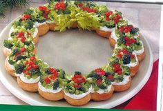 Christmas Appetizer Wreath 22 oz. tubes of crescent rolls 18 oz. package of softened cream cheese ½cup sour cream 1tsp. dill weed ⅛tsp. garlic powder 1½ cups broccoli florets (chopped) 1cup celery (finely chopped) ½cup sweet red pepper (finely chopped) Celery leaves