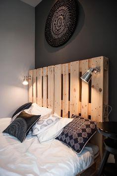 chambre à coucher d'ambiance feutrés avec des accents déco ethniques chic et une tete de lit en palette