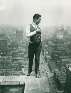 1930s USA, a man balances nonchalantly on a ledge high above the street.