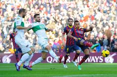 Alexis Sanchez |(R) of FC Barcelona shoots towards goal under a challenge by Alberto Botia (C) of Elche FC during the La Liga match between FC Barcelona and Elche FC at Camp Nou on January 5, 2014 in Barcelona, Catalonia.