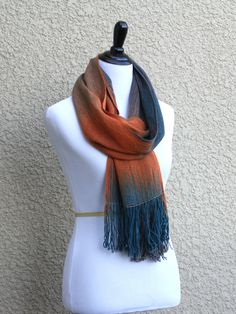 Woven scarf with gradually changing colors from teal to orange and beige…