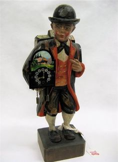 Musical wood figuarl. His head turns and he whistles a tune.Hand carved and painted. Carried in his arm is a (working) cuckoo clock. German