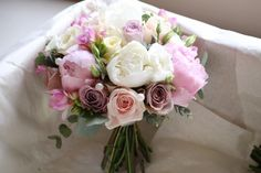 ivory, pale pink and vintage pink handtied bridal bouquet of ivory Avalanche roses, ivory paeonies, pale pink Sweet Avalanche roses, vintage pinky lilac Memory Lane roses, freesias and eucalyptus. From wedding at Botleys Mansion