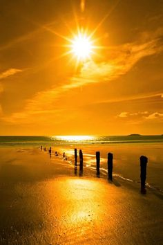 Golden sunshine over the beach breakers and blue Atlantic sea in Youghal County, Cork Ireland on a summers day.