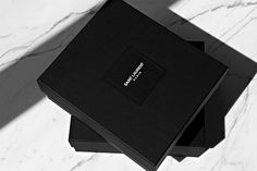 A Look at New Saint Laurent Paris Packaging: With Hedi Slimane recently assuming the role of Creative Director at fashion house Yves Saint Laurent, numerous branding alterations have been made. This week saw the first images of newly branded Saint Laurent Paris packaging, which takes the form of a modern and aesthetically minimal typeface.