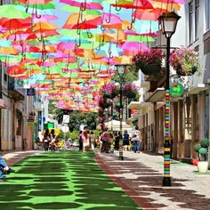 Pioggia di colori ad Agueda, in Portogallo    Foto di Patricia Almeida    Sospesi a mezz'aria gli ombrelli colorati in una splendida installazione artistica.    Guardandoli è come se stessero galleggiando sulla strada tra gli edifici di Agueda, in Portogallo.  L'installazione è un'iniziativa del Consiglio, nella piccola città appena a sud di Porto, e fa parte di un festival d'arte chiamata Agitagueda.