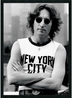 Love Lennon? Decorate With An Iconic John Lennon Music Poster. In This Black & White Photography Portrait, The Famed Beatles Frontman Strikes A Casual Pose In A Classic New York City T-Shirt. - Artist