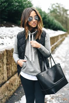I love the sunglasses, the black vest, the dark pants, the grey sweater, the black leather bag.