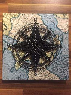 Beautiful hand String Art compass wall plaque mounted on 12 x 12 plywood mount covered in a vintage style map. A unique piece of art designed to stand out in any home