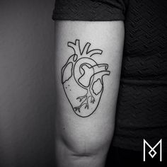 Continuous line anatomical heart tattoo on the back of the left arm.