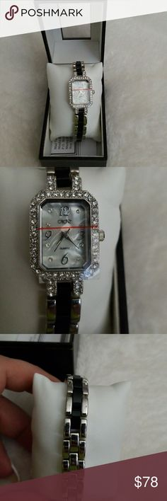 Cache elegant Mother of Pearl face Watch NWOT Cache elegant Black and Silver tone bracelet band. Crystals surround the bezel covering the Beautiful square Mother of Pearl Face of this time piece. Protective cover still over bezel. Time for the Holidays.. Be Fabulous Cache Accessories Watches