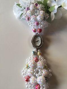 Die Armbanduhr (65) besteht aus vielen kleinen, weißen Glasperlen, weiß schimmernden Strassperlen und aus mehrfarbigen Perlen aus Glas. Außerdem hat sie eine verstellbare Verlängerungskette. Alle meiner Uhren können sie in meinem Shop bei etsy erwerben unter dem Namen PerlenweltDesign