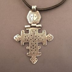"FOR OVER 1600 YEARS, THE CHRISTIANS FROM ETHIOPIA SUSPENDED FROM THEIR NECKS CROSS-PENDANTS, SYMBOL OF THEIR FAITH … THESE USE THE NAMES OF TOWNS OR VILLAGES WHERE THEY COME FROM … IN THIS CASE, IT IS A CROSS WORN BY WOMEN ""AMHARA"" FROM LALIBELA , HEADTOWN OF THE COUNTRY DURING THE TENTH CENTURY : THE COMPLEX CROSS LINES AND INTERLACING PATTERNS OF THAT CROSS DATES IT FROM THE 19TH CENTURY .  metal & mineral"