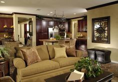 Lush cherry wood cabinetry throughout the kitchen area in this shared open space contrast with beige walls and tile flooring, while brown roll arm sofa and dark wood coffee table pair with twin leather ottomans.