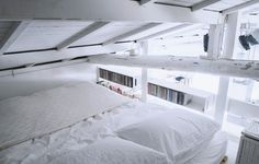 Quarto todo em branco, numa área de dormir tranquila, com teto inclinado