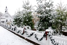Pretty snow covered trees and garland on a fence...love the white church in the background