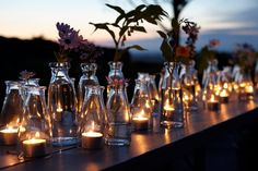 Bottles of flowers interspersed with candle bottles.  Enchanting.