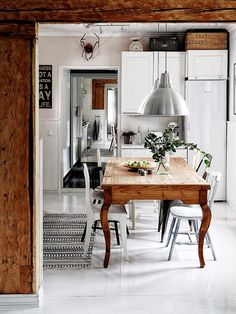 Industrial kitchen with a silver IKEA pendant light, a vintage wood table, and mismatched dining chairs