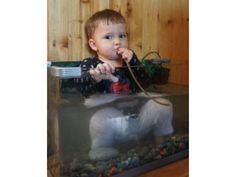 Ja, das Kind sitzt im Aquarium und trinkt das Wasser der Fische.