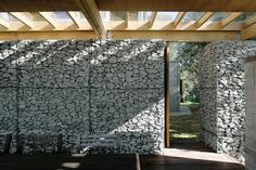 Covered terrace with gabion baskets | Great Barrier Island bach by Herbst Architects