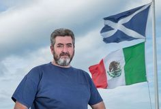 David Milne poses for a photograph beside the Mexican flag and The Saltire, the flag of scotland on the top of his house, located around 400 metres away from the Donald Trump's International Golf Links course, north of Aberdeen on the East coast of Scotland, on June 21, 2016..Milne, a long-term enemy of Donald Trump has raised the Mexican flag within clear sight of the White House hopeful's golf course in protest, ahead of the tycoon's visit to eastern Scotland on Saturday. / AFP / Michal…