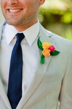 Terno claro e flores bem alegres e coloridas na lapela do noivo. Muito charme e alegria para o verão!