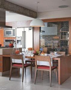 """PARA AMANTES DA GASTRONOMIA. Após a demolição da parede que separava a cozinha da sala, restou uma viga. """"Como ela ficaria muito evidente, resolvemos descascá-la e deixar o concreto aparente, textura que acaba valorizada pela madeira e pelas cores da cozinha"""", acredita o arquiteto Fernando Dainese."""