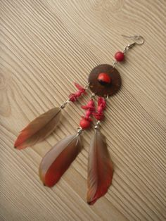 This earring has the size of about 14 cm and is decorated with red feathers of Amazonian parrot and a seed of guairuro, that indigenous people consider a means of protection from negative energies.