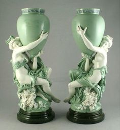 A pair of large Minton Porcelain figural vases, modelled with semi-clad maidens and Amphora, after a model by Carrier, glazed in shades of green and white.