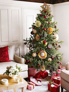 Paper medallions and classic red ornaments create a festive, homespun feel on this tree! Get more how-tos here: http://www.bhg.com/christmas/trees/christmas-tree-pictures/?socsrc=bhgpin112514craftychristmastree&page=5