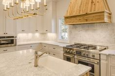 A TT Linear Branched 10 Light Chandelier hangs over a white kitchen island topped with white quartzite fitted with a farmhouse sink and faucet.