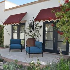 White stucco, black doors, crimson awnings, blue chairs