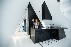 The modern matte black kitchen has been designed to perfectly fit the triangular shape of the interior, with the angles accentuated by the strong contrasting lines of the cabinetry.