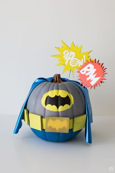 """Pumpkin painted in gray, blue, and yellow—including a blue fabric cape—to resemble Batman's costume from the television show based on the DC comic book character. Starbursts on top of the pumpkin say """"KAPOW!"""" and """"BAM. Superhero Halloween, Halloween Kids, Halloween Crafts, Halloween Decorations, Halloween 2020, Cheap Halloween, Outdoor Halloween, Pumpkin Decorating Contest, Pumpkin Contest"""