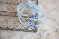 A pretty, pale blue yarn tieback, embellished with natural dried moss, gypsophillia, a blue flower and a pearlNewborn size