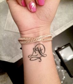 Modèle tatouage deux lettres entrelacées pour un poignet.