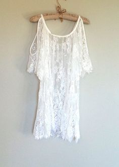 This beautiful sheer white lace, Boho tunic length, open shoulder top is so elegant and drapey. Its cold shoulder features hangs beautifully off the body and can be worn as a top or a dress.  Throw it over a swimsuit for a bohemian, effortless beach cover up. Pair it with jean shorts and boots ...