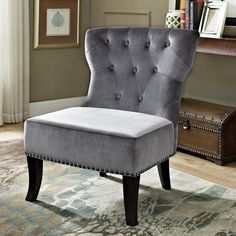 The Waterloo Chair has a classic, curvaceous shape made modern by its tapered, curved legs and beautiful velour upholstery fabric. This accent chair features pewter nail head detailing and tufted back