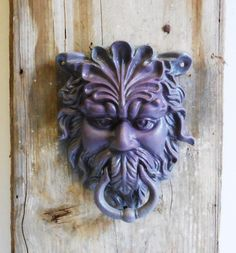 Cast iron door knocker. Painted a dusky plum that blends out to gray with bits of red showing through. Some natural imperfections in the making. See photos for further condition and details.  Measures approx. 7 x 9 inches