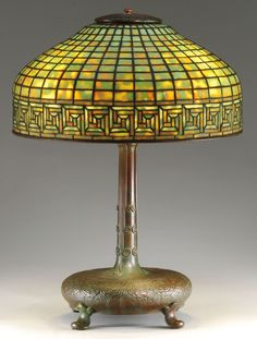 A Tiffany Studios Greek Key table lamp features a background of mottled green and yellow panels that would come to life with a turn of a knob.
