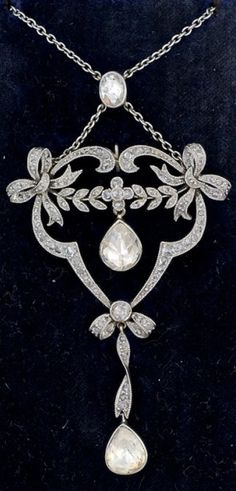 A Belle Epoque platinum and diamond pendant, by Bonebakker, The Netherlands. Of openwork garland style with bows and flowers, set with small rose-cut diamonds, suspending two pear-shaped rose-cut diamonds. #Bonebakker #BelleÉpoque #pendant