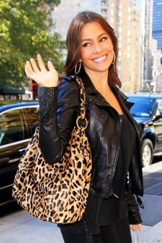 Black leather jacket, black shirt, black jeans, black shoes, leopard print tote.