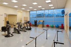 The existing high structural bays of the former supermarket lent themselves well to creating high ceilings for large spaces like the physical therapy gym and wellness room. These rooms were designed to provide a flexible space that can be opened for larger groups or closed off for separate activities. Photo: Steve Wolfe Photography