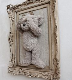 Attach a stuffed animal (hot glue or stitch) onto burlap and then place in an open frame. (Idea only ~ No instruction on website)