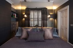 The guest bedroom mixes a dark canvas with a serene finish. The dark brown walls encompass elements of a gloss finish, emphasised by the sheer curtains and fabric draperies. On either side of the window, two contemporary wall-hung lampshades add a subtle golden shine to the spacious room. #bedroom #bedroomideas #luxurybedroom #sheercurtains #bed #lamps #bedsidetable #cushions