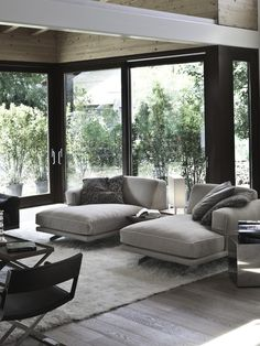 contemporary gray living room with glass walls ,comfortable contemporary chaises high ceiling and weathered gray wide plank floor